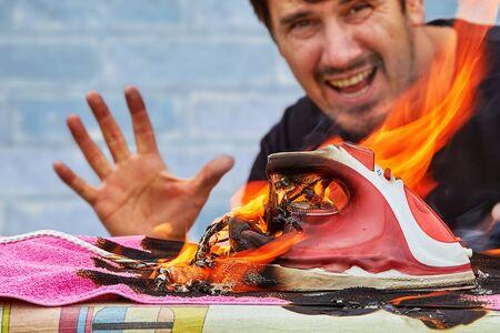 Un hombre está tratando de apagar un incendio doméstico, una plancha eléctrica para planchar se sobrecalienta y se incendió en una tabla de planchar.