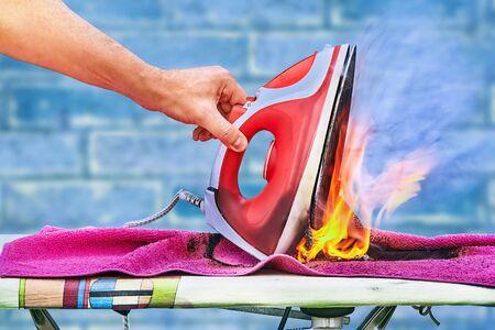 Na desce do prasowania zapaliło się przegrzane żelazko do ubrań, w domu wybuchł pożar, ręka podnosi zwęglone żelazko. Plastik stopił się, pościel spaliła.