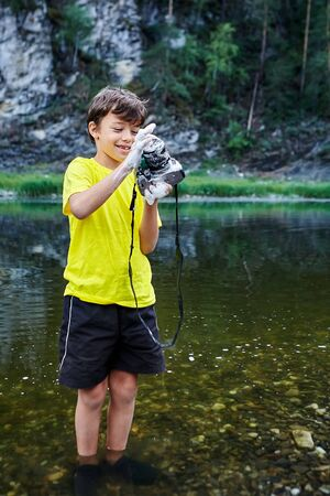 A naughty boy, dressed in shorts and a yellow T-shirt, washes a digital SLR camera lens using soap and water from a forest river. Water got inside the camera and the gadget broke.
