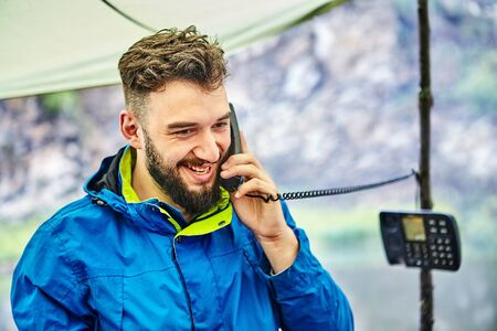 One man uses a wired push-button telephone. A young man enjoys talking on an outdated landline phone in nature. Handsome bearded Caucasian man smiles during a fascinating telephone conversation.
