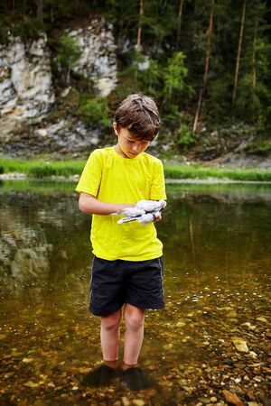 A little boy in a yellow T-shirt and shorts is standing on a shallow in the water of a forest river and is using soapy foam to display a mobile phone. Mischievous broke phone their parents.