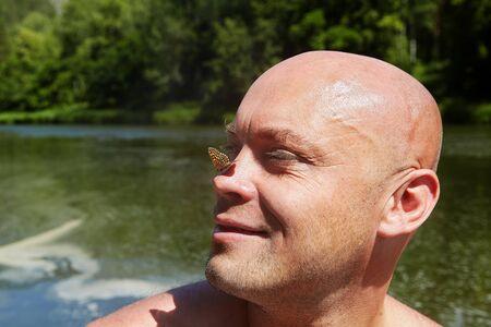 Un hombre calvo descansa en estado salvaje en el ecosistema de un río forestal, sonríe cuando una polilla se posa en su nariz. Ecoturismo en las reservas naturales de Rusia.