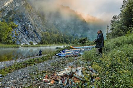 Water tourists in their camp at dawn. Rafting enthusiasts meet a misty dawn on the banks of a mountain river. Ecotourism in the mountains of the South Urals, Russia.