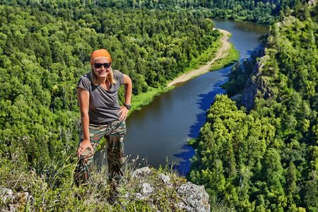 A smiling woman in a bandana and sunglasses stands on top of a mountain, against the background of a quiet forest river flowing below, a hiker is engaged in ecotourism in Russia on a sunny summer day. Stok Fotoğraf