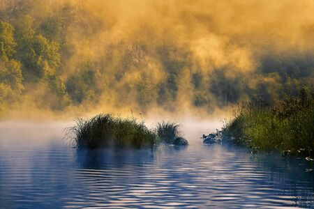 Morning fog over the river is illuminated by the rising sun. A quiet river flowing in the Ural rocks, a place of ecotourism in Russia. Stok Fotoğraf