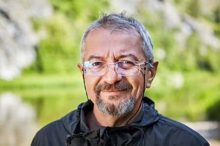 Street portrait of an educated man of Caucasian ethnicity, 56 years old, wearing glasses in a thin metal frame and a small beard. The intelligent face of a good-natured mature man.