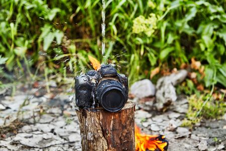 The camera left near the fire was charred and melted. The camera was burned from the flames of a tourist campfire, and fell into disrepair. A photographer pours water on a camera destroyed by fire.