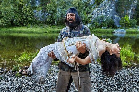 Un anciano brutal y entristecido sostiene en sus brazos a una mujer inmóvil con un vestido de noche en el fondo de una orilla pedregosa de un río salvaje en medio de la vida silvestre. El anciano rescata a una dama indefensa. Foto de archivo