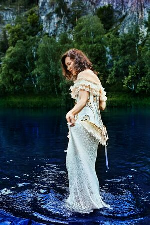 A lady in an evening or wedding dress with embroidery, walks on the blue river water in the evening, against the backdrop of wildlife. The bride went into the water of a wild river. Stock Photo