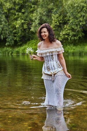 A beautiful  woman in a dress with a corset, with bare shoulders, walks on the water along the river bank with a bouquet of wildflowers in her hands. Lovely woman in wedding or evening dress outdoors.