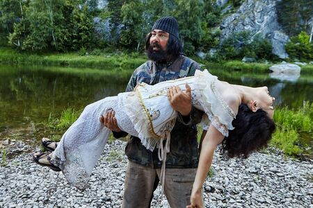 A fisherman carries a woman dressed in a wedding dress from the river bank. The woman is in a state of drug or alcohol intoxication, she lost consciousness. The bearded fisherman saved the girl.