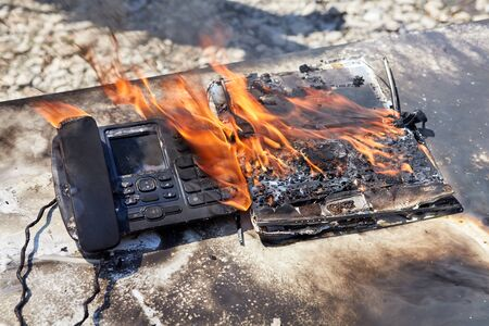 A fire in the office, a flame destroys a wired telephone and laptop, an office desk ignited. A landline telephone burns in an office fire. Imagens