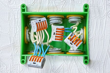 Installation of a plastic junction box for home wiring, electrical wires spliced using a spring terminal block with a push lever for five contacts. Electric wire connector.