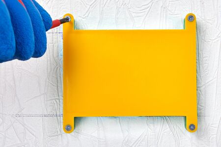 Repair and maintenance of home electricity, electrical work. Junction box for concealed wiring under drywall. A repairman secures a yellow protective cover over the distribution panel.