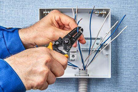 Installation de fusibles automatiques sur rail DIN. Câblage de bricolage d'une unité de consommation ou d'une installation de tableau de distribution. Dénudage de l'extrémité du fil de cuivre avec l'outil de coupe.