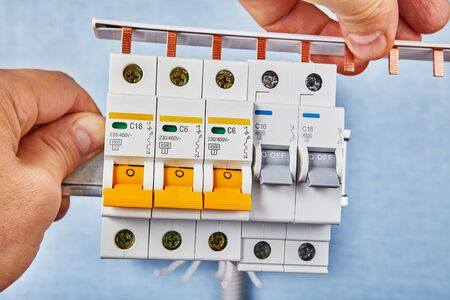 Miniature circuit breakers perform the dual functions of a switch and a fuse. Electrician is installing the connection busbar for the automatic fuses. Electrical installation work, home wiring repair.