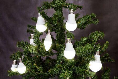 Der Weihnachtsbaum ist mit elektrischen LED-Haushaltslampen in der Farbe Weiß matt geschmückt. Energiesparende und energieeffiziente Beleuchtung, kreative Idee für die Dekoration des neuen Jahres zu Hause. Leuchtdiode.