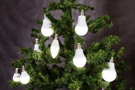 The Christmas tree is decorated with household LED electric lamps in white matte color. Energy-saving and energy efficient lighting, creative idea for home New Year decoration. Light-emitting diode.