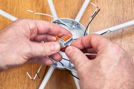 Splicing electric wires in a electrical box of a ceiling chandelier using a spring-loaded lever terminal block. An electrician mounts a wiring of a lighting device by connecting  cables in connector.