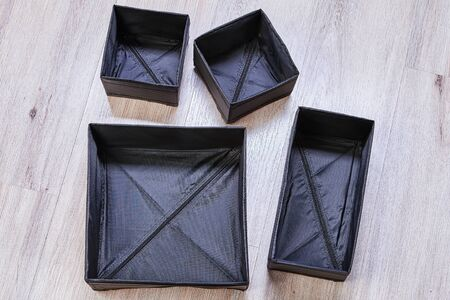 Folding boxes of black color, of different sizes and shapes, are designed for separate storage of garments in drawers, these containers are dividers for storing clothes. 版權商用圖片