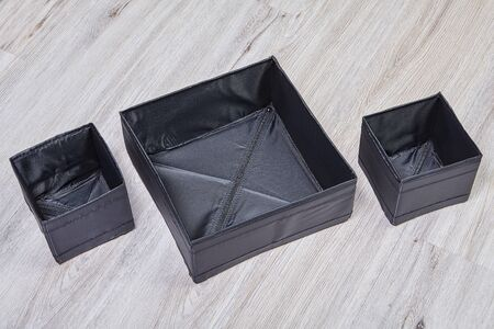 Set of black foldable storage boxes of cloth. Box for separate storing of linen in a drawer.