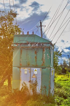 An old distribution transformer substation in the countryside, made of metal sheets, painted green, and equipped with warning signs.