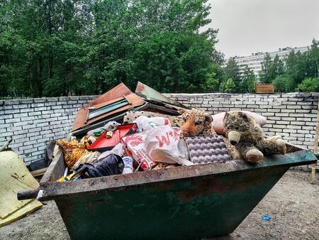St. Petersburg, Russia - June 9, 2019: Crowded steel dumpster without separate collection of household waste. Soft children's toys thrown in the trash.