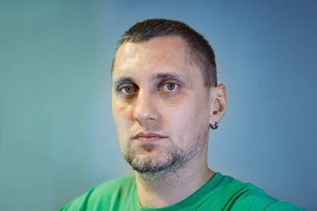귀에 귀걸이를 한 40세 남성의 클로즈업 초상화. 군인, 의사, 외과의사, 게이머가 될 수 있습니다. 짧은 머리와 수염을 기른 40대 남성.