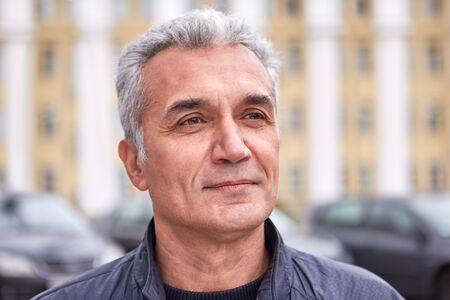 A successful well-groomed man over 50 years, short gray hair, a pleased look, casual clothes, the face of a politician, TV presenter or doctor. Middle-aged man with delicate features, smart appearance Stockfoto