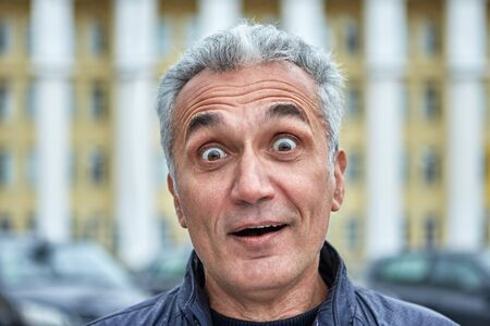 Closeup portrait of a surprised man with short gray hair and over 50 years. Middle-aged male with pop-eyed in the outdoors. Astonishment in the eyes of businessman or official near government building Stock fotó