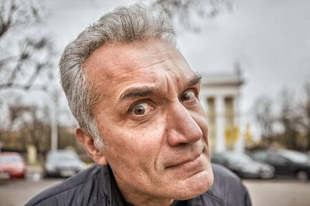 An annoying middle-aged man with a questioning look pestering someone on the street. A male over the age of 50 with short gray hair, a Caucasian ethnic, demanded looks into the interlocutors eyes.