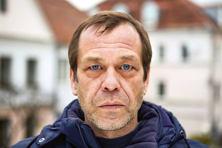 A serious face of a Caucasian middle-aged man, over 50, close-up, he is an emigrant, unemployed, or has problems. Street portrait of a sad male of fifty years old, in a European city, closeup.