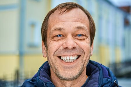 Cheerful Caucasian middle-aged man over 50, close-up smiling unshaven face with white teeth and blue eyes. A happy white male of fifty years old on a city street in Europe.