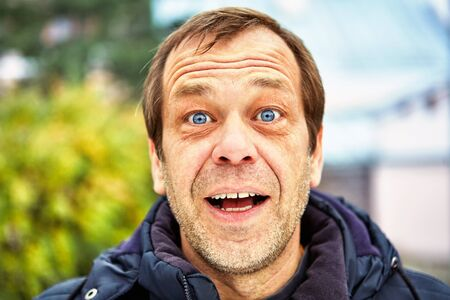 The surprised face of a man of fifty years old against the background of a European street, close-up. Head of a joyful middle-aged male over 50 outdoors. Unshaven elderly Caucasian with blue eyes.