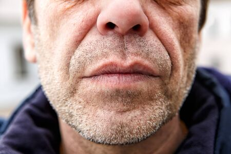 The lower part of the unshaven face of a middle-aged man, 50 years old, it is possible that he is a manual worker or an unemployed emigrant. Bristle on the face of a male that looks like a robber.