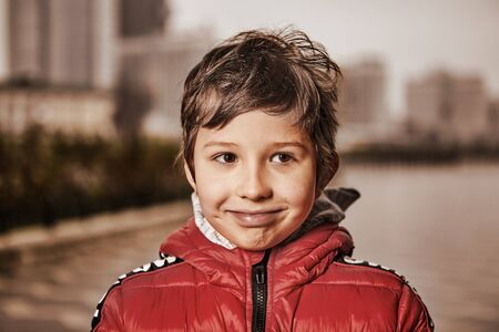 One boy of seven years old, in warm clothes, stands on a city street in cold, cloudy weather with a smile on his face. Portrait of a cheerful child in a red down jacket outdoors. Archivio Fotografico