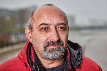 Nahaufnahme-Straßenporträt eines älteren Mannes mit Glatze mit grauem Bart in warmer Kleidung. Das Gesicht eines Mannes mittleren Alters, der älter als 50 Jahre im Freien ist. Fünfzig Jahre alter Geschäftsmann draußen bei kaltem Wetter.