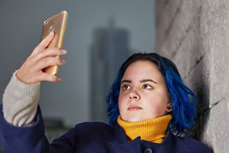 A young woman with dyed blue hair and a coat of the same color uses a smartphone to take a selfie, or to shoot video outdoors in the evening. A chubby girl photographs herself with a mobile phone.