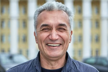 Closeup laughing face of an elderly businessman, civil servant, doctor or television presenter. Portrait of a joyful caucasian man over fifty years, with short gray hair outdoors, near public building Stockfoto