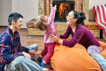 Same couple and their little daughter are sitting on the bean bag chair, playing and smiling near fireplace. Two women with stepdaughter are spending evening together.