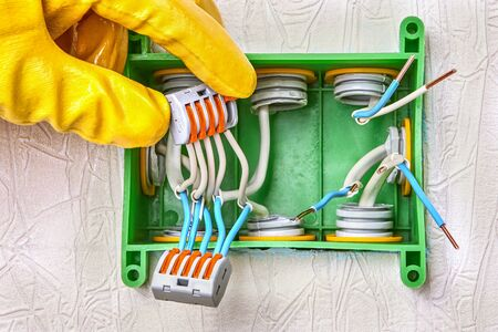 Use of a connector with a spring lever clamp for splicing conductors inside a square junction box made of green plastic. Connection of electrical wires inside terminal block. Electric installation.