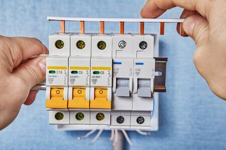 Installing new consumer unit with automatic fuses or circuit breakers. An Electrician use connection busbar for mounting fusebox. Installation of switchboard or distribution board. Electrical service. Stock Photo
