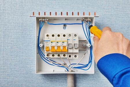 The installer installs an electrical switchgear in the house. Mounting the fuse box inside the electrical cabinet, the electrician tightens the bolt in the neutral terminal to secure the wire. Stock Photo