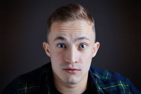 The wide eyes of a young man who watches a film in a movie theater, or at home on TV. Frightened or surprised face of a caucasian guy, close up, on dark background. The white boys startled gaze.