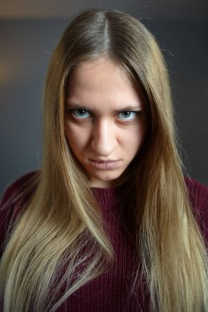 A sullen look from under the eyebrows on the angry face of a long-haired Caucasian girl, dark blue 写真素材