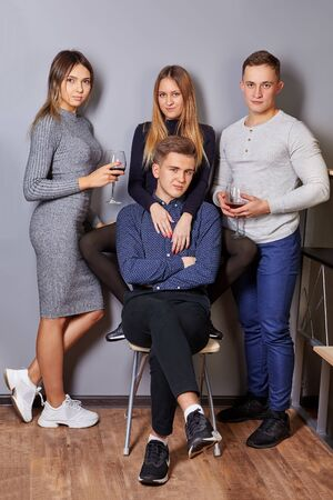 Young men and women take photos for social networks during student party in a college dorm. Lovely girls and attractive men posing for photographer at event. Portrait of a group of females and males.