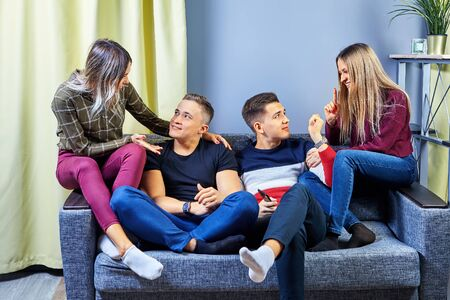 Students chatting in one of the college dorm rooms. Young men and women play intellectual games in an apartment or dormitory. Two couples in love on a double romantic date communicate on a soft sofa.