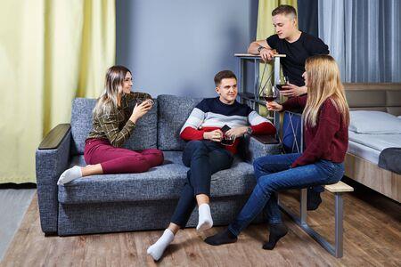 Des amis se sont rencontrés lors d'une fête dans un dortoir ou un appartement pour étudiants. Les jeunes parlent, rient et boivent du vin ou une autre boisson alcoolisée. Les jeunes hommes et femmes sont assis sur un canapé dans une chambre de dortoir universitaire. Banque d'images