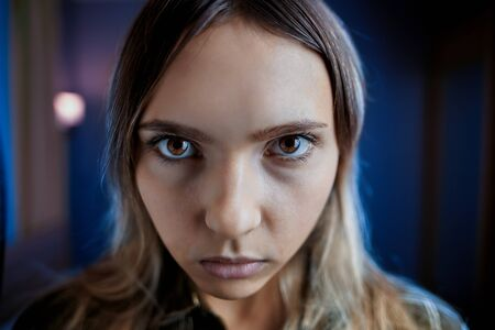 Offended jealous woman with mental disabilities spitefully looks from under her eyebrows. Young paranoid female with a gaze of brown eyes, face close-up on a dark room in blue tones.