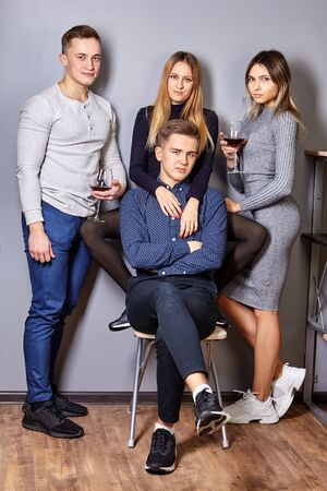 Friends posing for a group portrait at a student party. Young men and women with glasses of wine in their hands, looking at the camera. Two couples in love at a joint photo shoot while drinking.